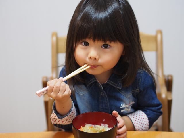 お箸でごはんを食べる子供