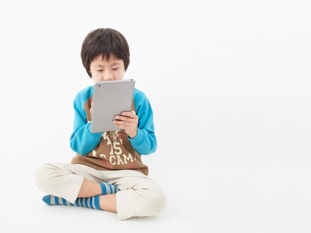 タブレットの操作をする子供