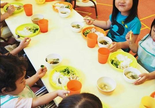 夜間幼稚園でご飯を食べる子供