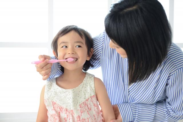 母親と一緒に歯磨きをする子ども